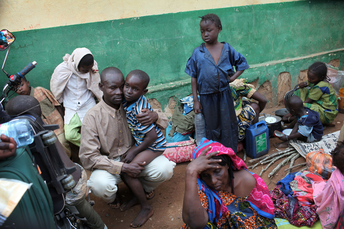 A peul family wait for treatment after the son got wounded by a machete .Hundreds of people wait at PK12 to flee bangui and go to the Chadian border.