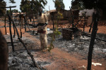 A man stand next to his burned house in a village on the road between Boali and Bangui.