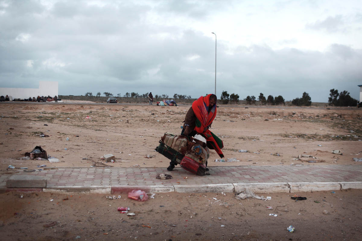 An Egyptian man  who were working in Libya carry their belongings after they fled the country at the Tunisia-Libyan border, near the town of Ben Guerdane,Tunisia