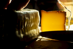 Slicing a brick of smoked cheese as the late afternoon sun streams through the kitchen sindow.