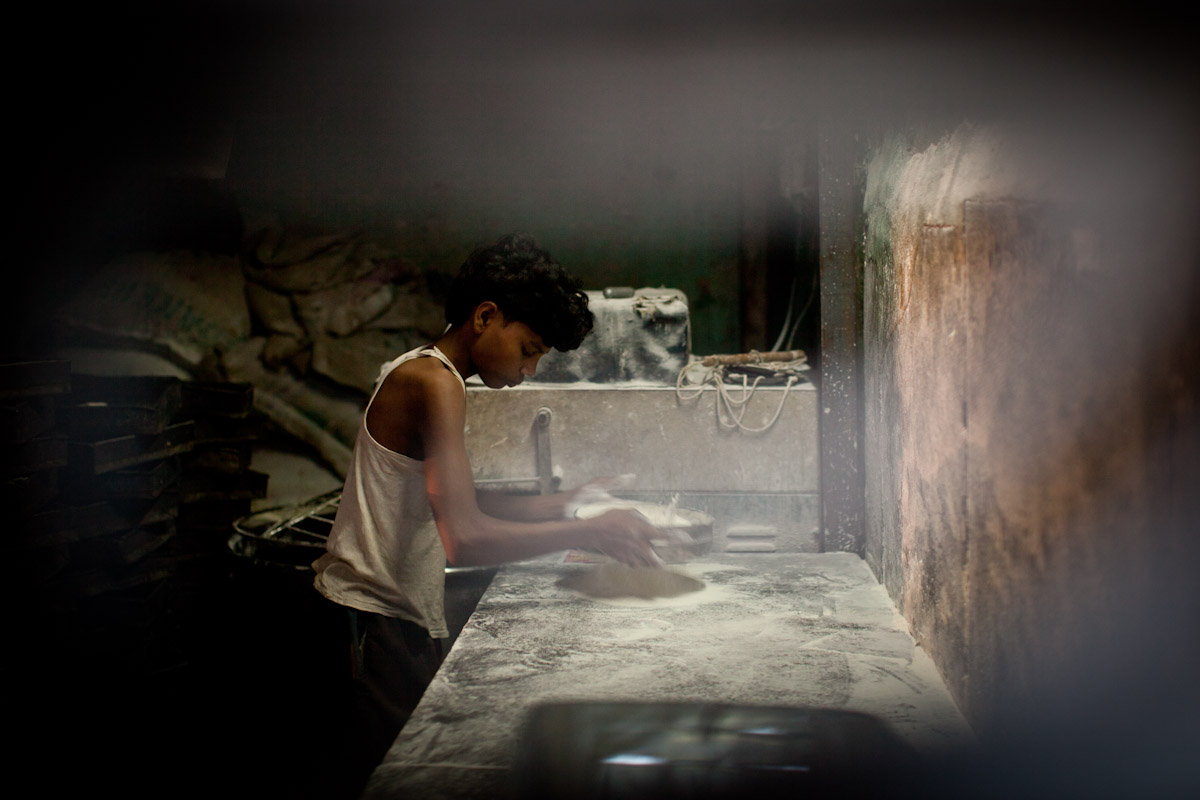 A young boy prepares bread in one of the many ad-hoc bakeries set amongst the industrial part of Dharavi.
