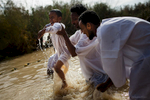 Christian Orthodox pilgrims and refugees from  Eritrea perform a baptism ceremony during the day of the Epiphany at the 'Qasr el Yahud' baptism site in the Jordan River Valley, near the West Bank city of Jerico. The Epiphany celebrates the baptism of Jesus, which is belived to be in this same location