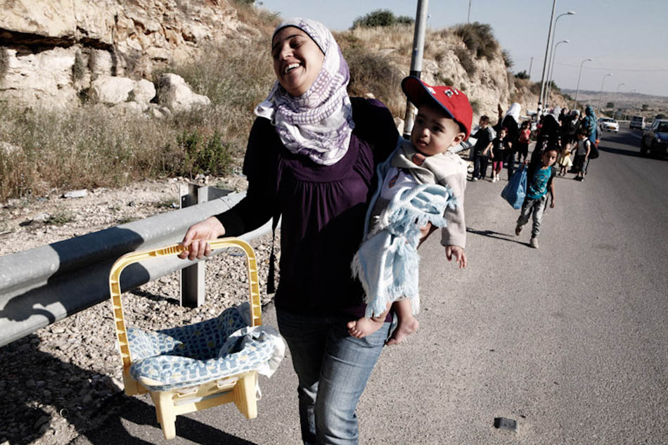 Palestinians mothers and children on their way to the Israeli checkpoint in Ramallah. As Palestinian vehicles are not permitted to cross the Israeli border, they needed to leave the bus 500 meters awayfrom the border and enter the country on foot.