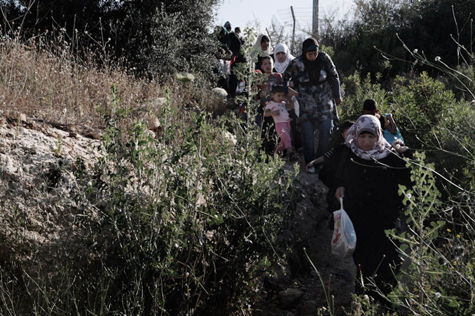 Palestinians mothers and children on their way to the Israeli checkpoint in Ramallah. As Palestinian vehicles are not permitted to cross the Israeli border, they needed to leave the bus 500 meters away from the border and enter the country on foot.