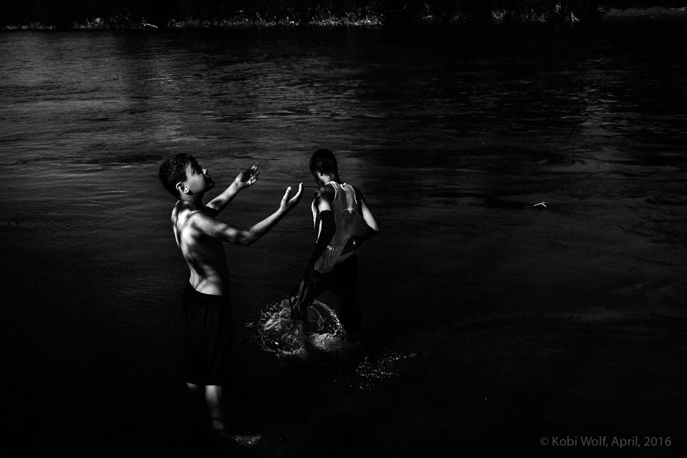 Young Syrian refugees swim in the river  at the Macadonia - Greece border
