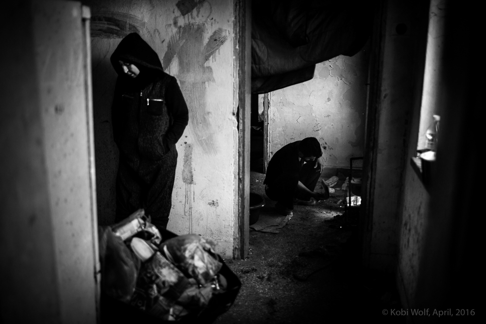 Syrian refugee inside a small room in a desetred buliding at the train station in Idomeni.