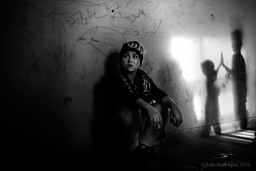 Syrian refugee woman inside a small room in a desetred buliding at the train station in Idomeni.