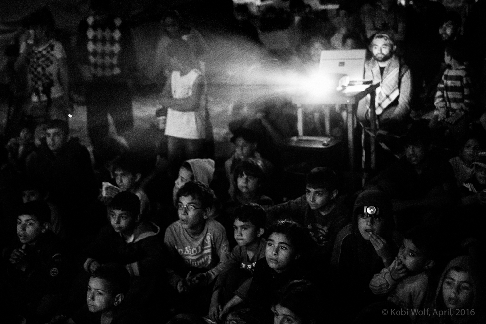 Children watching a cartoon movie in the refugee camp of Idomeni , Greece - Macedonia border