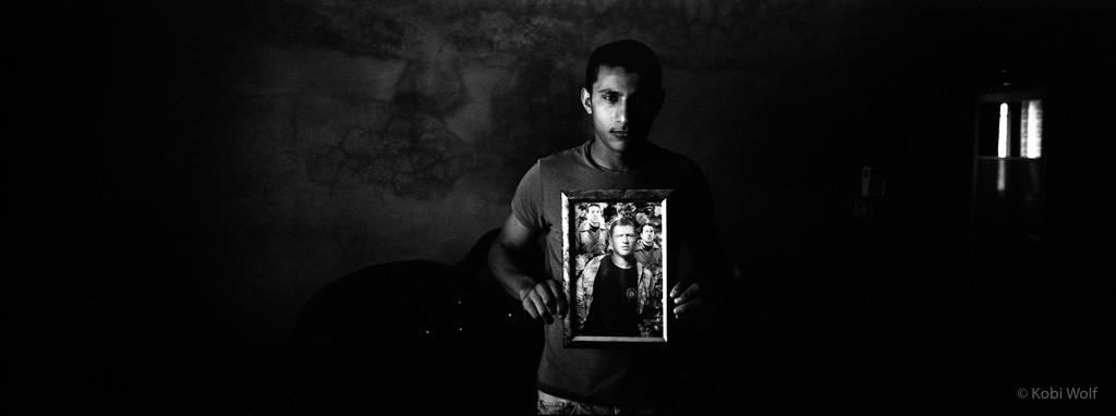 Basat Daragme holding a picture of his Brother Muhanez who was killed by an unexploded bomb when he was 18.