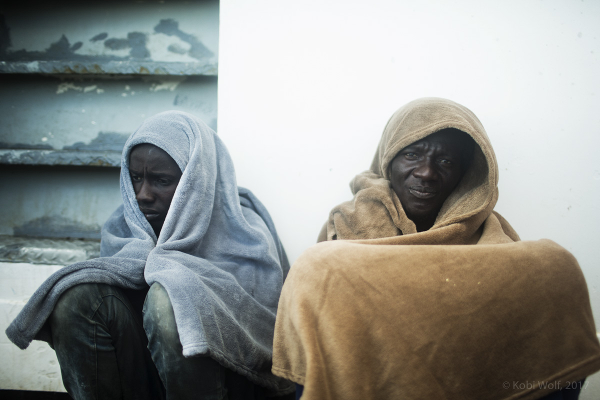 Migrants rest on the deck of the Procativa open arms ship  after being rescued in the central Mediterranean, in international waters off the Libyan coastal town of Sabratha.