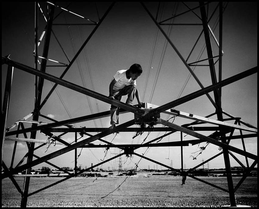 A kid playing on a power facility at Wadi al-Na'am. The village is encircled by a large facility of the national electric company as well a hazardous industrial park and military areas including a live-fire range.