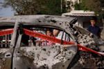 Curious People watch a car damaged by a direct hit from a rocket Fired from Gaza in Ashkelon, Israel on May 11 2021 photographer: Kobi Wolf