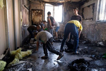 Schoolchildren clean out debris from a damaged Yeshiva classroom, following overnight protests in Lod, Israel, on Wednesday,