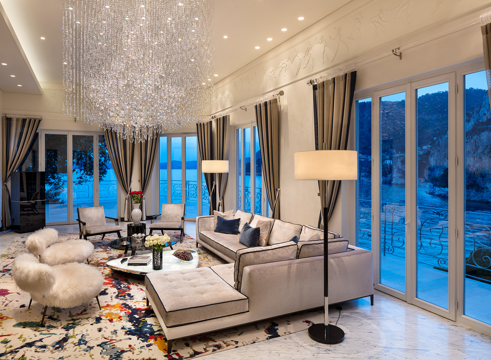 Wide view of opulently furnished living room of luxurious super-prime Villa built into cliff at premier location next to Monaco.