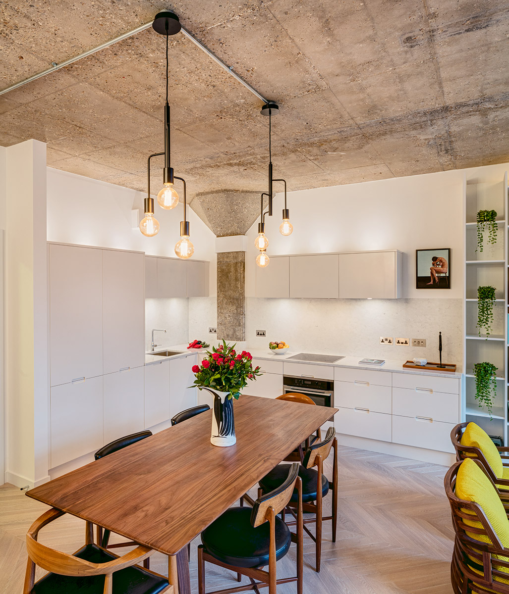 Kitchen area with concrete walls and large wooden table in furnished loft apartment of complete internal redesign project of former warehouse building in Shoreditch. Interior Designer - Warret Julien