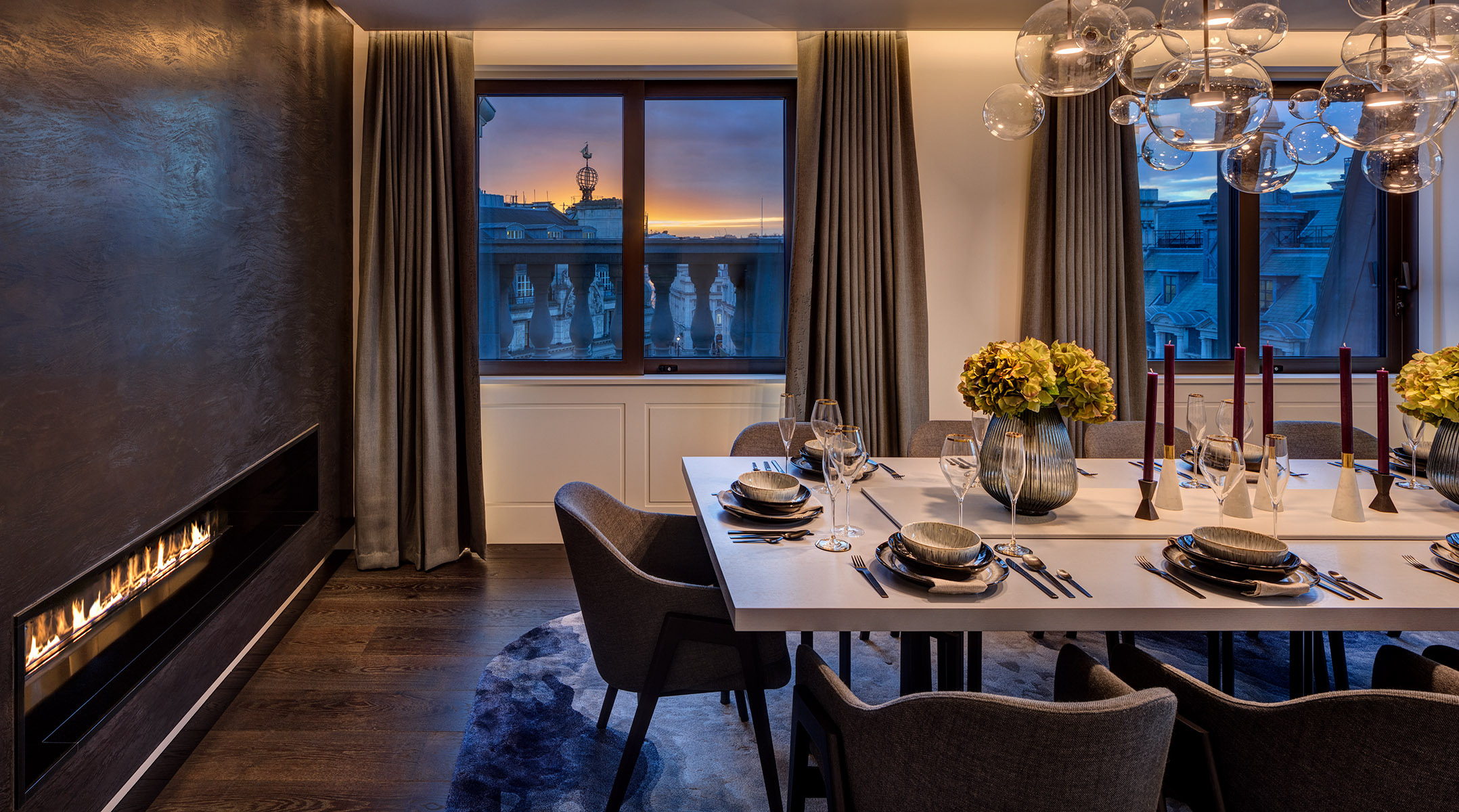 Photograph of a dining area with contemporary fireplace and a view out to London rooftops at sunset.
