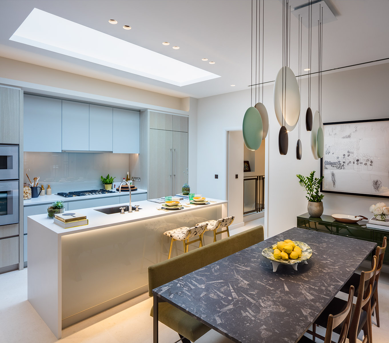 Dining / Kitchen area of contemporary interior design apartment in Russell Court. Large slate table with high-end bespoke internal fixtures and fittings in kitchen