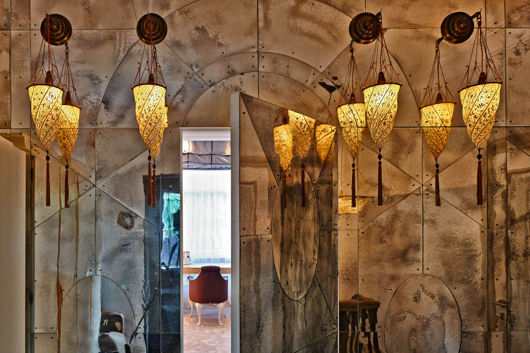 Detail of landing area in Private House in Èze with Moroccan style lanterns and distessed mirrored wall and door