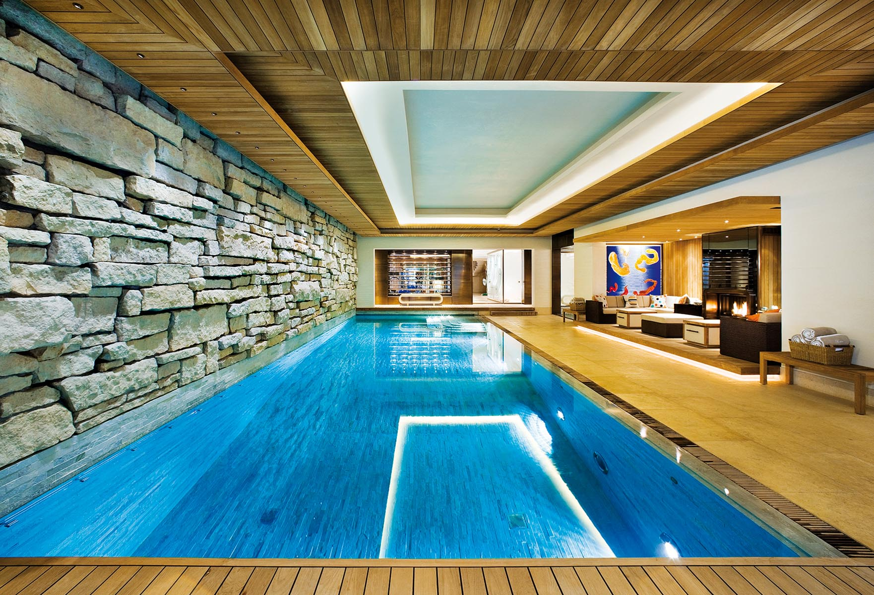Large swimming pool in private residence with feature stone wall and layered pine ceiling with view to spa area