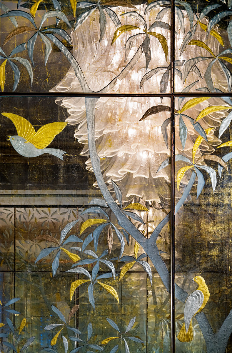 Mirrored wardrobe detail with etched gold leaf design of birds and plants with feature candelabra in reflection
