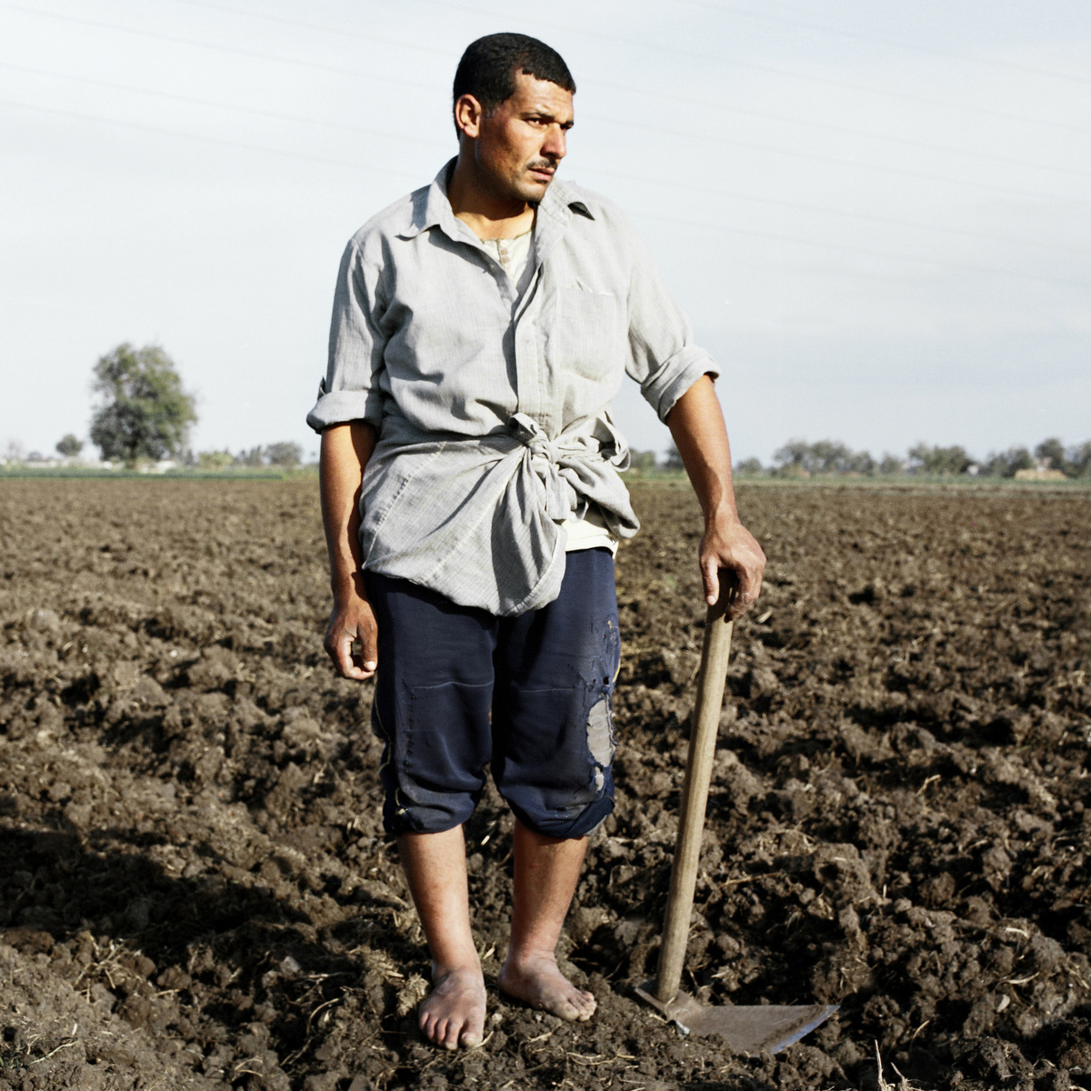 A farmer pauses while working in the field.
