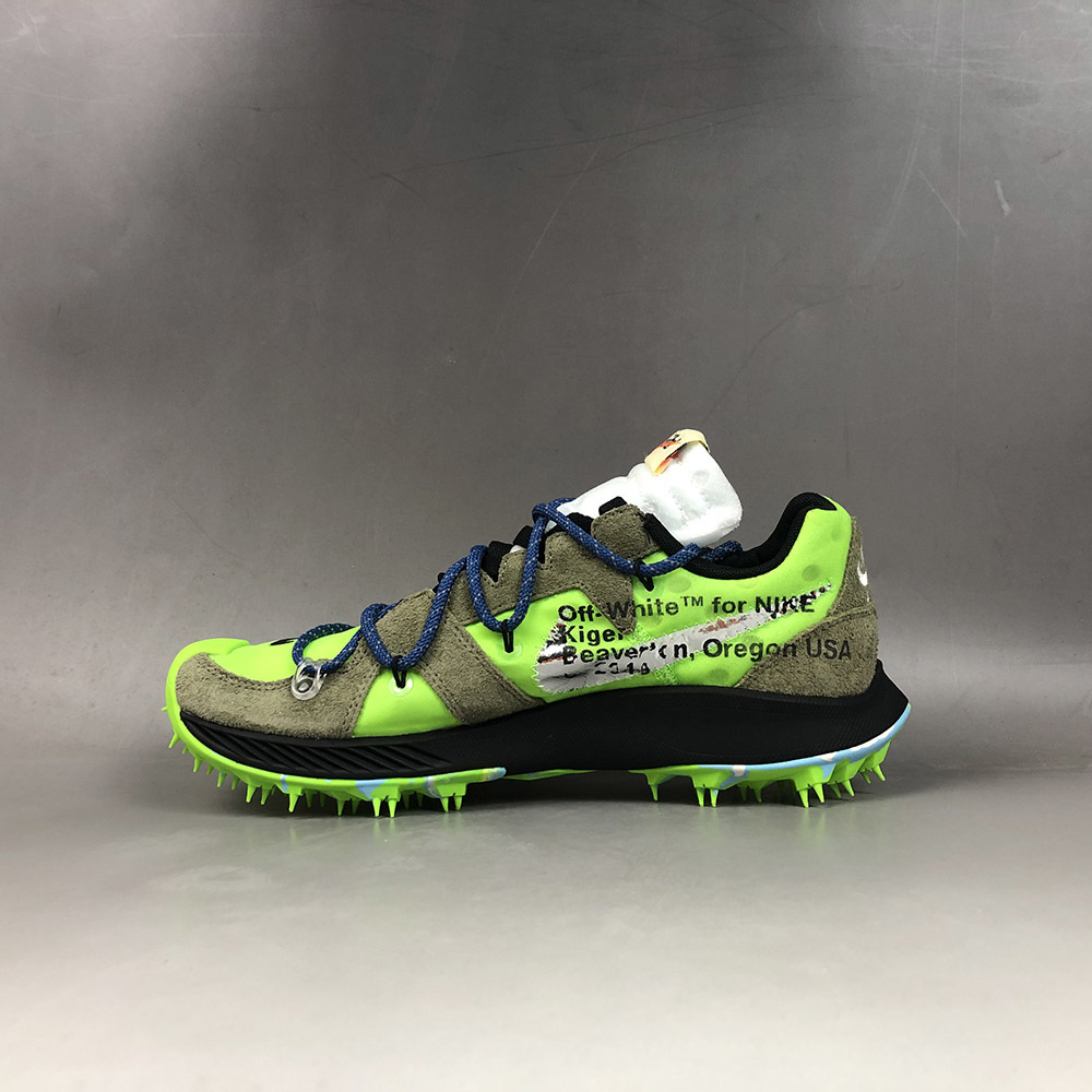 """Virgil ABLOH (b. 1980)Outer: Nylon 100%, Suede 100%Sole: Rubber 100%9 1/8 in (23.3 cm) = U.S. Women's Size: 6.5The Off-White x Zoom Terra Kiger 5 """"Electric Green"""" is one of the three debut colorways for the unique silhouette by Virgil Abloh. The bold design features the Zoom Terra Kiger 5 trail running shoe with a radical makeover by Abloh, modified with recognizable Off-White design cues including premium materials, exposed foam on the tongue, printed text, and an orange tab. Abloh also adds a bold auxiliary lacing system and the model's most distinct detail, the spiked rubber outsole. This colour way features an Electric Green textile base with suede overlays in olive and black accents for the Swoosh branding and midsole. The spiked sole matches the neon green hue of the upper with marbled hits of bright blue mixed in. The signature Off-White zip-tie appears in green for the final touch.Please click HERE for full fact sheet"""