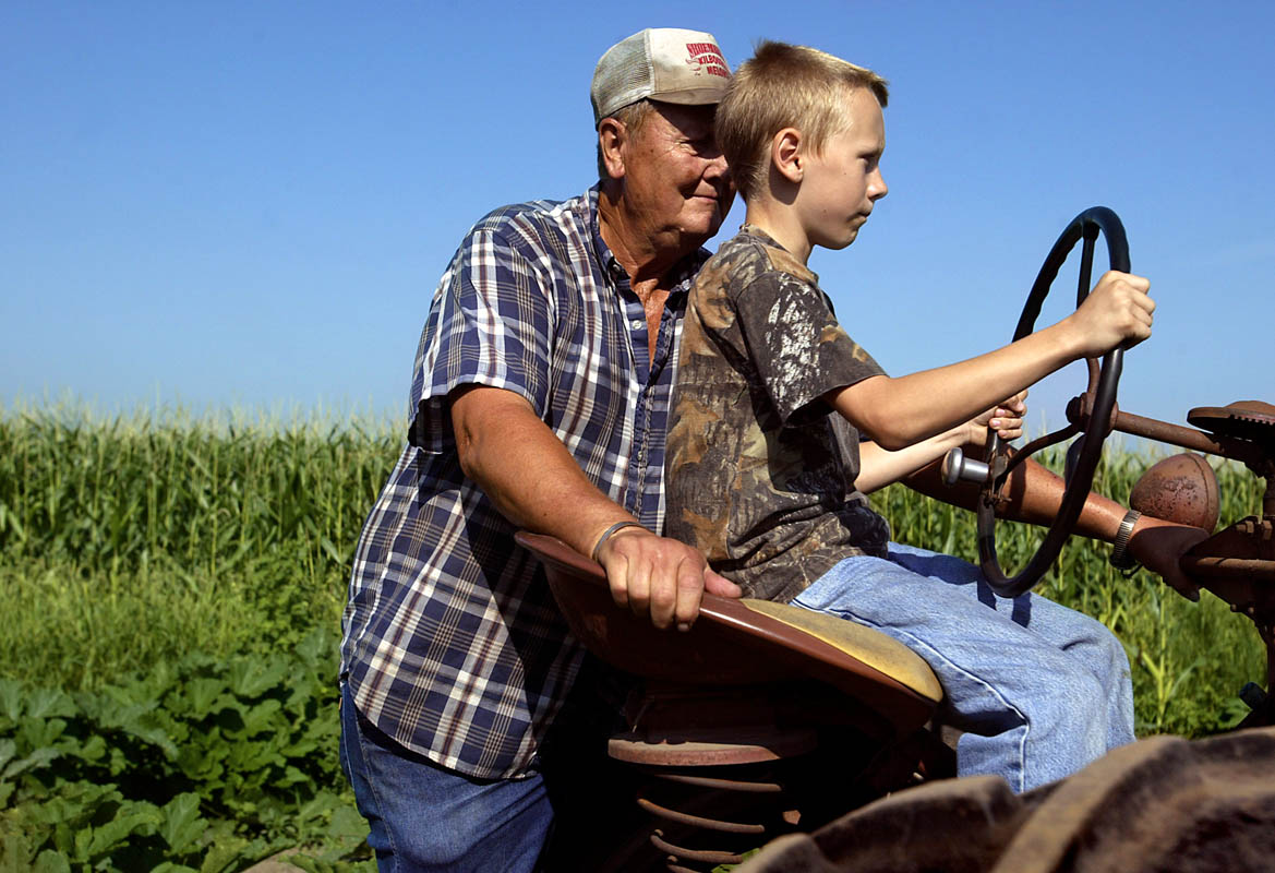"Lee Shoemaker, 65, teaches his grandson Brody Shoemaker, 10, how to drive an antique tractor while harvesting cantaloupe from the sandy soil of their farm in Kilbourne, Ill. ""Just let (the clutch) out slow,"" says Lee. Brody pipes up: ""This thing is jerky!"
