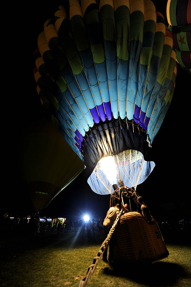 At the Third Annual Hot Air Balloon Festival in Santa Paula, Calif., on Friday, July 30, 2010 a group of men light up the hot air balloon with flames during the Glow event while people crowd around and watch. {quote}It takes about twenty minutes to blow up the balloon,{quote} Dean Davey said from start to finish.
