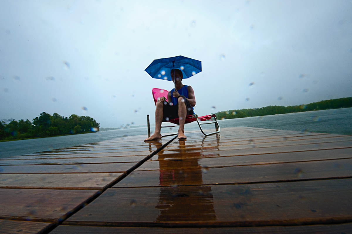 Zach Reidinger, 17, from Lake Forest, Calif., alone on a dock holds an umbrella while on a lawn chair enjoying the pouring rain on his family's dock at Kelly Lake in Suring, Wisc., on September 2, 2010. Reidinger has been visiting the lake every summer since he was 10 years old, but he has never been there in September and definitely felt the difference in the weather.