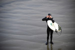 Dillan Kenny, 24, from Pismo Beach, is catching a glimpse of his girlfriend on the pier after surfing waves on Saturday, January 22, 2012 next to the Pismo Beach pier in Pismo Beach, Calif. This was the first time Kenny was able to surf in front of his girlfriend.