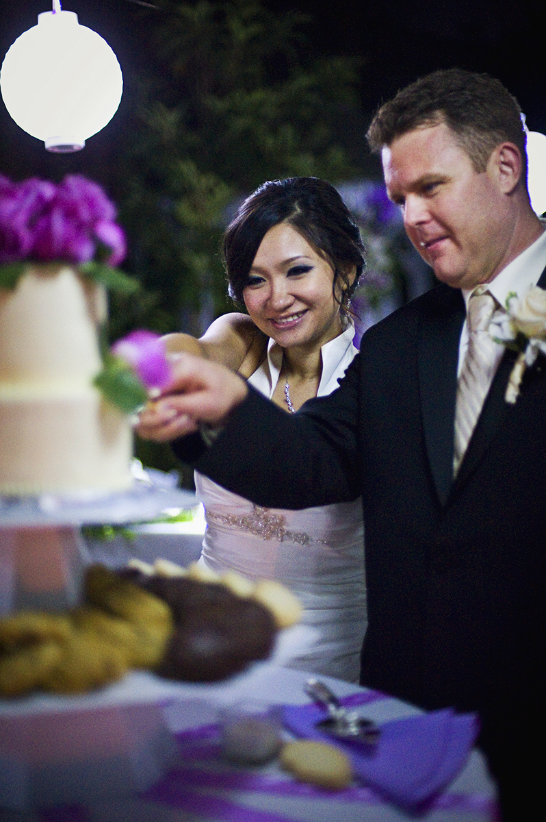 Groom, Jeff Grant, 38, from Huntington Beach, Calif., is cutting the cake with his bride, Eva Wu, 30, from El Monte, Calif., at their reception  at an ocean view home in Malibu, Calif., on Saturday, October 27, 2012. Wu and Grant fed each other a piece of cake successfully using only their hands.