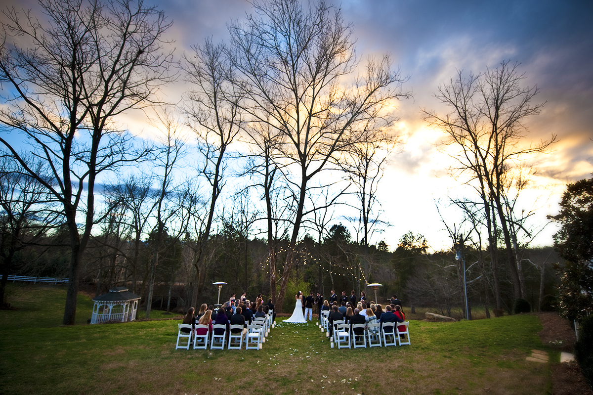 The ceremony for Sarah and Duncan Carlton takes place on the lawn during sunset near a subtly flowing creek at the Vesuvius Vineyard in Iron Station, North Carolina on Saturday, December 29, 2012. The bride choked up a bit with joy during her vows with her husband.