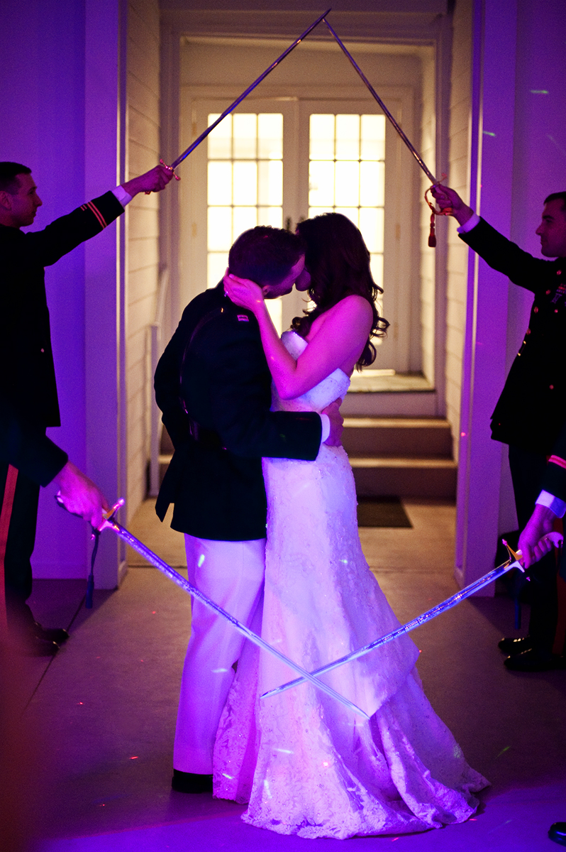 Groom, Duncan Mark Carlton, 26, from Laguna Niguel, Calif., kisses his bride, Sarah Ann Schultz, 28, from Laguna Niguel, Calif., to pass through the sword arch entrance at the reception in Iron Station, North Carolina at the Vesuvius Vineyard on Saturday, December 29, 2012. The evening was full of non-stop dancing from all ages between four generations!
