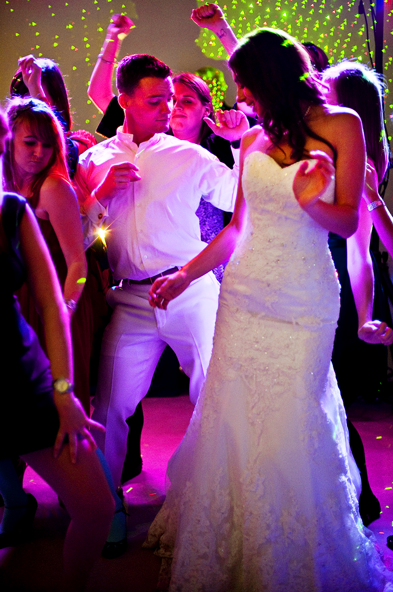 Groom, Duncan Mark Carlton, 26, from Laguna Niguel, Calif., dances with his bride, Sarah Ann Schultz, 28, from Laguna Niguel, Calif., and all their guests during their wedding reception to the song, {quote}Too Much Booty,{quote} by DJ Godfather at the Vesuvius Vineyard in Iron Station, North Carolina on Saturday, December 29, 2012. The evening was full of non-stop dancing from all ages between four generations!