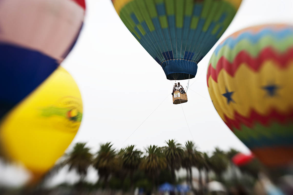 A group of people are lifted in the air held by lines to the ground while in a hot air balloon at the Third Annual Hot Air Balloon Festival in Santa Paula, Calif., on Saturday, July 31, 2010.