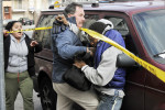 Jersey City police detective Robert Potter stops the distraught brother of murder victim, Ramona Pujols, from going into her apartment building on Central Avenue where she was found dead. Jersey City officers detained the brother, cuffed him and was taken away in a police car, after he continued to be uncontrollable at the crime scene. He was released later in the day. The main suspect, Pujols' boyfriend, William Davila, 36, was arrested the next day. (Reena Rose Sibayan/The Jersey Journal)