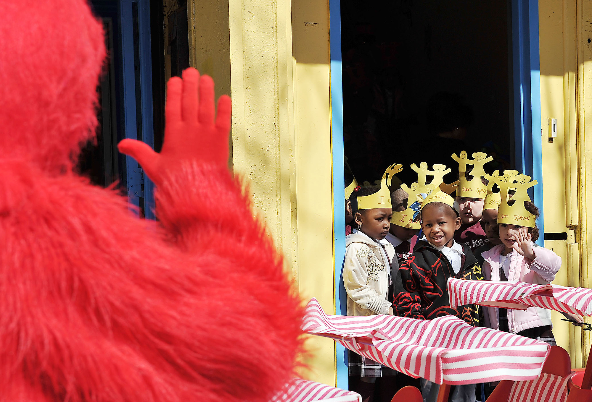 Pre-K students at the Kidz Kastle II on Ocean Avenue wave to Elmo as they prepare to march down the block in celebration of The Week of the Young Child. (Reena Rose Sibayan | The Jersey Journal)