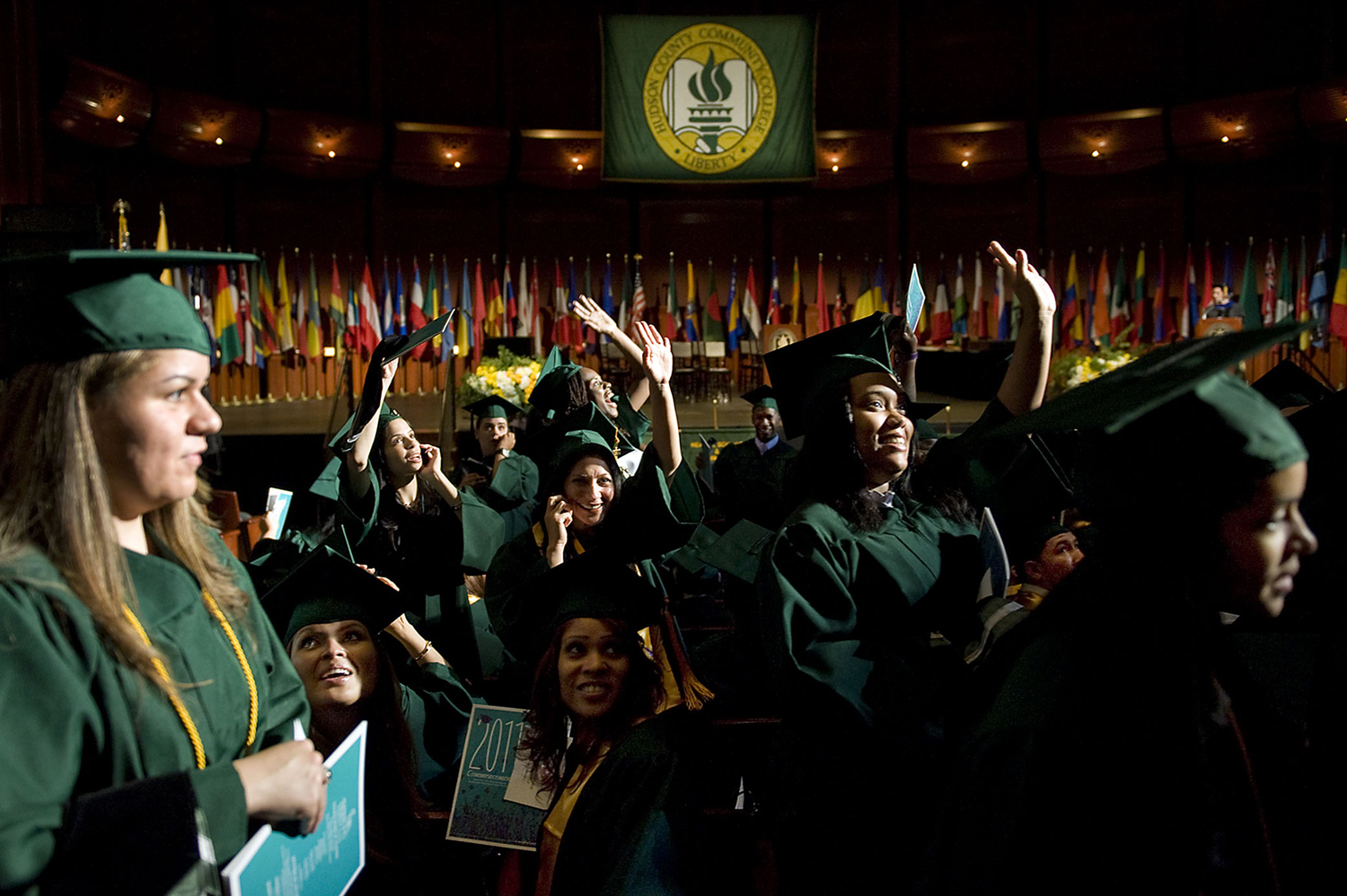 Graduates wave to the their loved ones in the audience before the start of the Hudson County Community College graduation ceremony at The New Jersey Performing Arts Center. (Reena Rose Sibayan | The Jersey Journal)