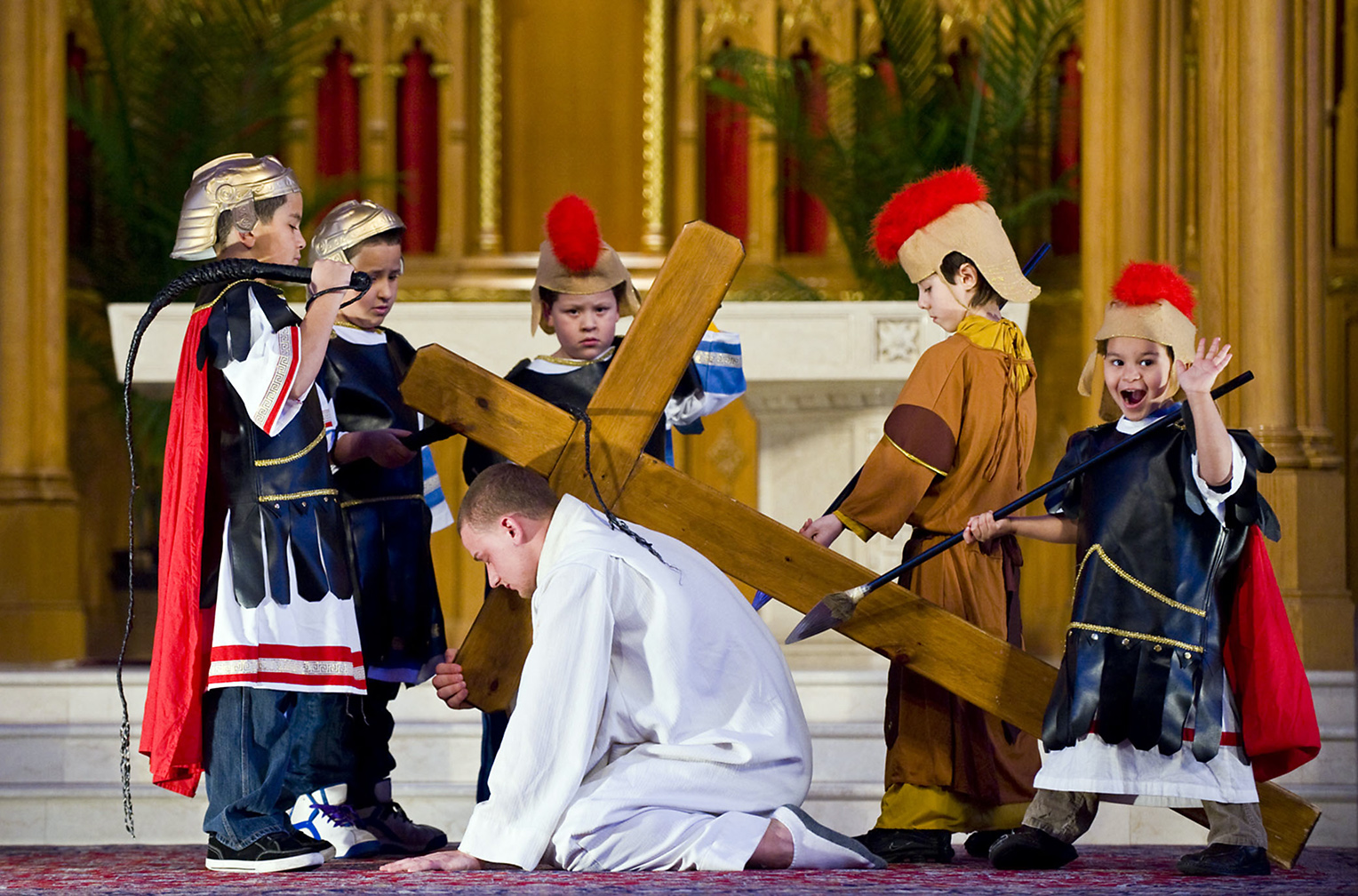 Students and teachers of St. Henry's Religious Education stage the Living Stations of the Cross–a series of tableaux depicting the last hours of Jesus Christ–at St. Henry's Roman Catholic Church in observance of the Christian holy day, Good Friday. Here, the Ninth Station: Jesus Christ (Jack Santopietro) falls for a third time. At right, Ezekiel Lupianez, 4, dressed as a Roman soldier, breaks character, when upon seeing his mother, Maria Lupianez, in the audience taking his picture, he breaks into a smile and waves for the camera. (Reena Rose Sibayan | The Jersey Journal)