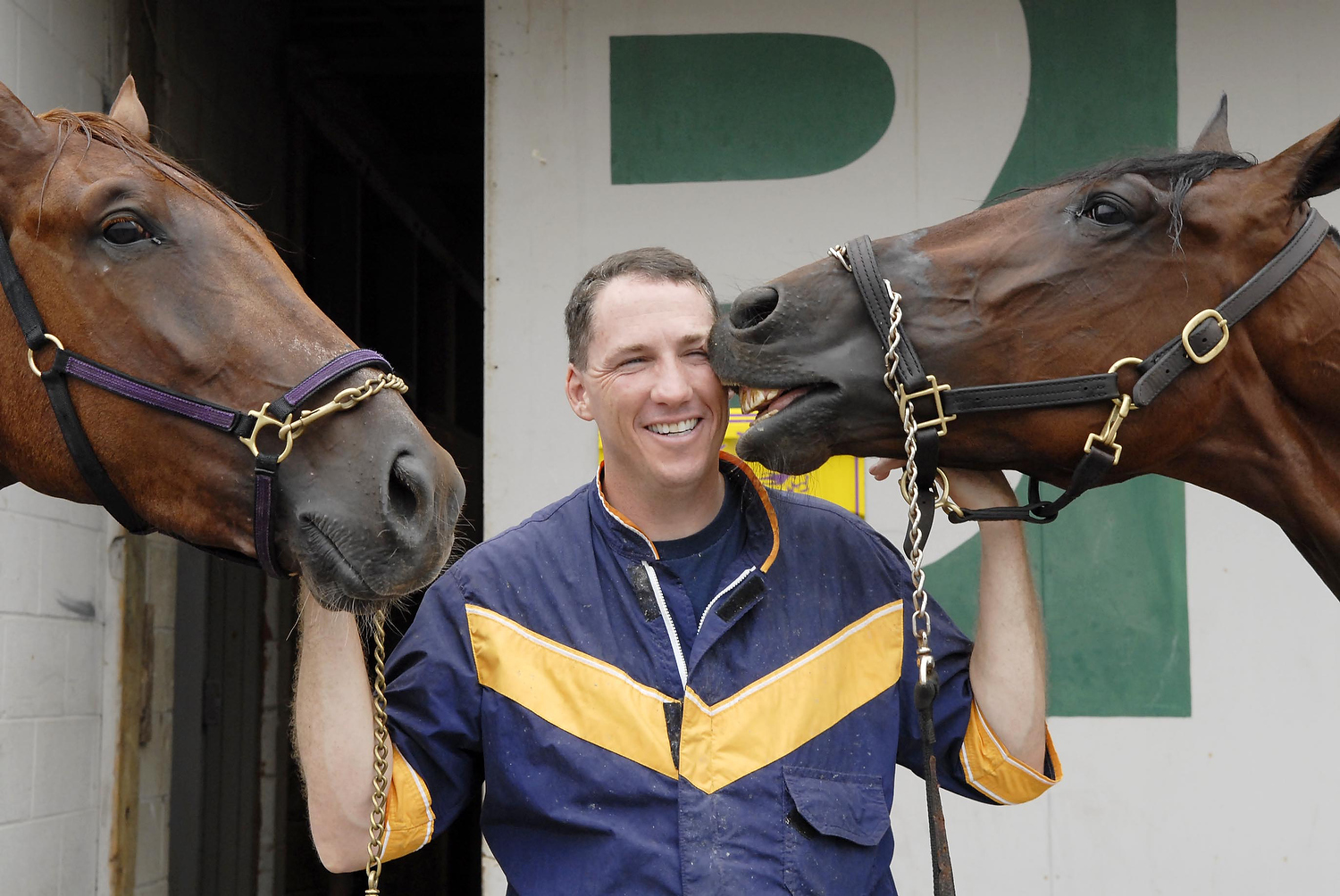 Horse trainer John McDermott,  with Real Mean Art, left, and Load the Dice, two horses he trains at the Meadowlands Racetrack. {quote}I grew up so close to this place, I feel like it's home,{quote} said McDermott, a former police officer-turned successful horse trainer. (Reena Rose Sibayan | The Jersey Journal)