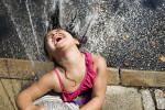 Lailani Susana, 5, plays in the spraying water of an open fire hydrant at the corner of Belmont and Bergen Avenues during a heat wave. (Reena Rose Sibayan/The Jersey Journal)
