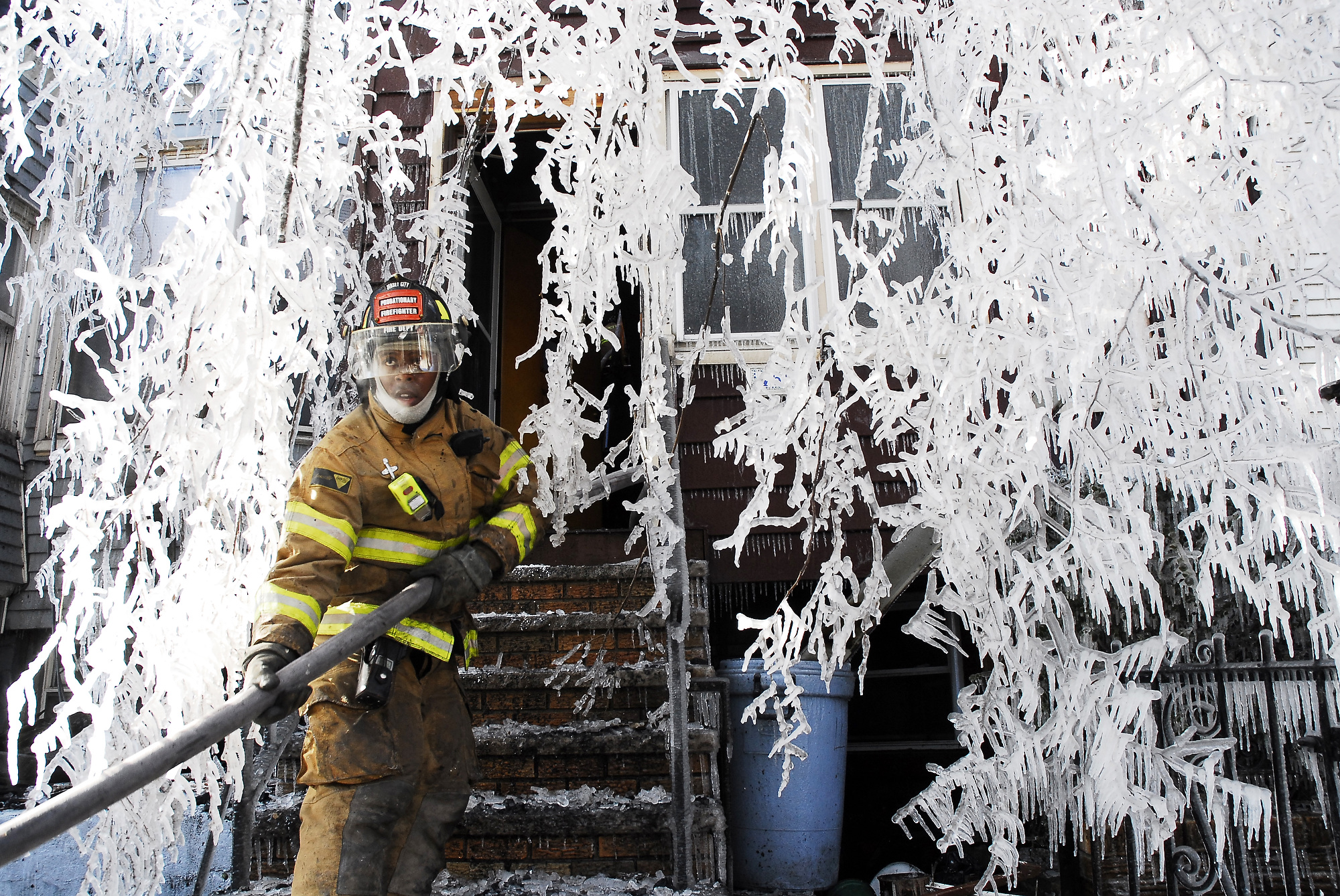 A firefighter drags a fire hose into one of four homes on Fairmount Avenue damaged by the four-alarm fire which also ripped through three businesses on West Side Avenue. Three firefighters were injured. (Reena Rose Sibayan | The Jersey Journal)