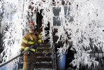 JERSEY CITY, N.J., FEB. 27, 2006 -- A firefighter drags a fire hose into one of four homes on Fairmount Avenue damaged by the four-alarm fire which also ripped through three businesses on West Side Avenue. Three firefighters were injured. (Reena Rose Sibayan/The Jersey Journal)