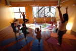 Genie Morrow, upper left hand corner, and Liza Bertini, lower right hand corner, lead a kids yoga class at Devotion Yoga. (Reena Rose Sibayan | The Jersey Journal)