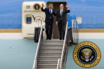 U.S. President Barack Obama and New Jersey Gov. Jon Corzine wave at the top of the steps as they exit Air Force One at Newark Liberty International Airport. (Reena Rose Sibayan/AP Photo)