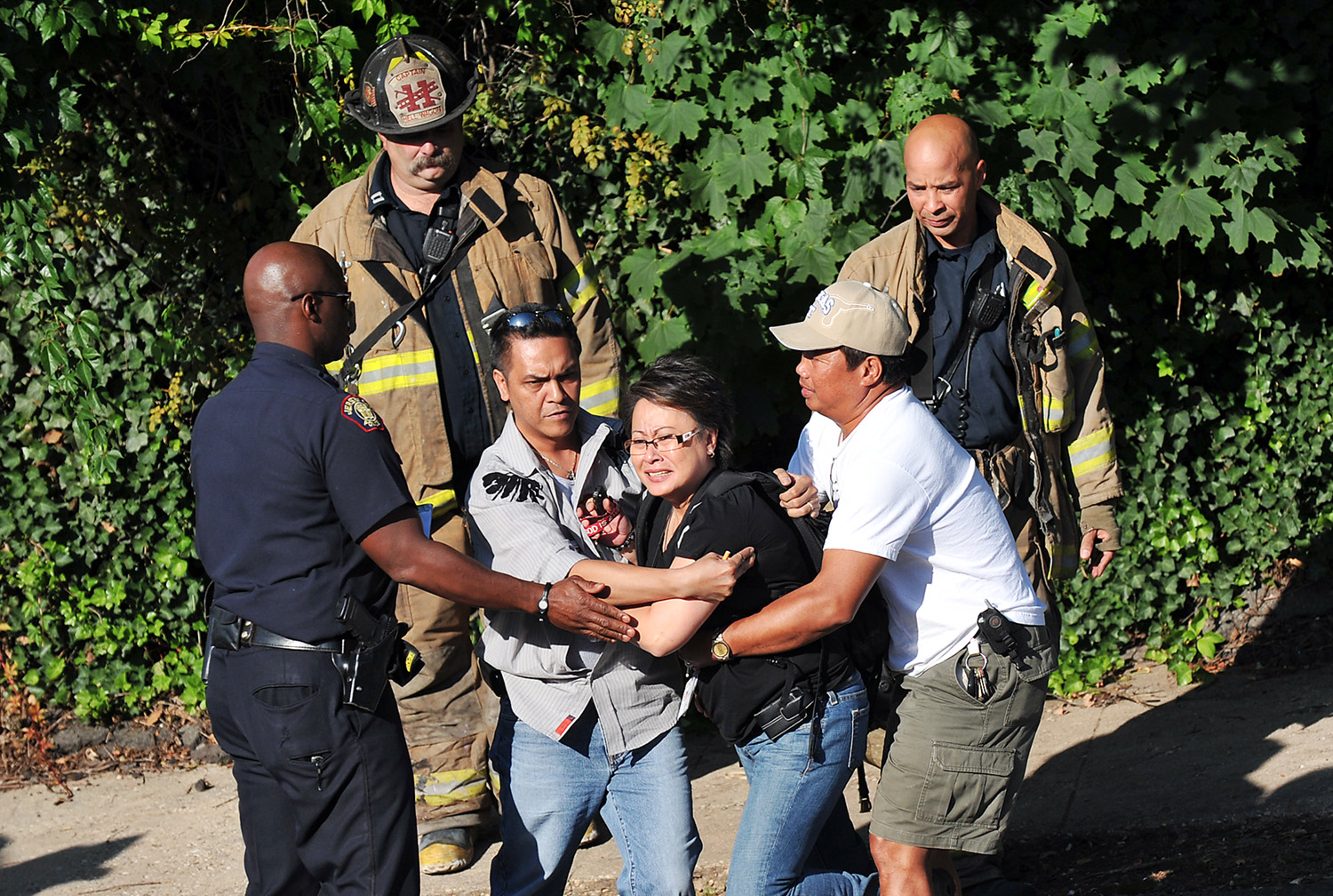 Friends try to restrain a distraught Miles Dionisio, sister of Christine Mariano, 20, who was found strangled to death in a fire at Mariano's Stevens Avenue home. (Reena Rose Sibayan | The Jersey Journal)