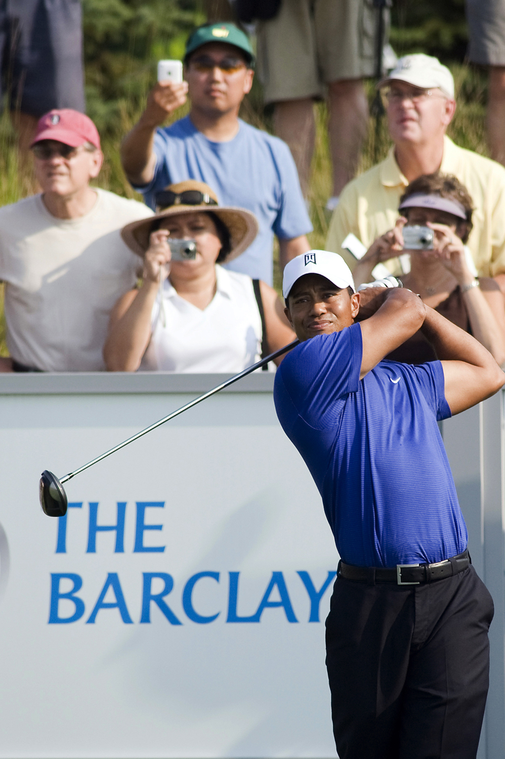 Spectators snap photos as Tiger Woods tee off at one of the holes during The Barclays Classic Pro-Am at Liberty National Golf Course. (Reena Rose Sibayan | The Jersey Journal)