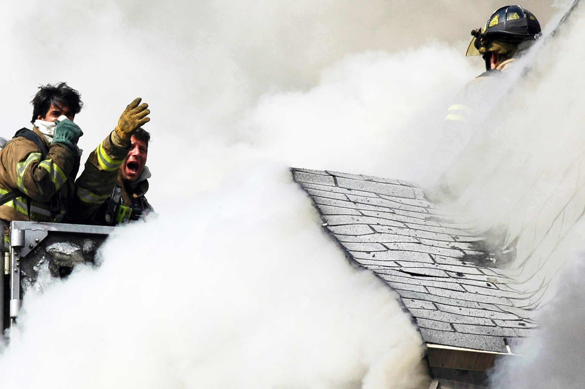 Firefighters reach out to others trapped on the roof of a house on Randolph Avenue while battling a three-alarm fire. The firefighters on the roof were rescued by those on the tower ladder. Four homes were damaged and four people were injured including three firefighters. (Reena Rose Sibayan | The Jersey Journal)