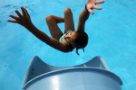 Eleven-year-old Kate Matthews shoots out of the water slide at the municipal pool on an 80-degree summer day. (Reena Rose Sibayan/The Clark Eagle)