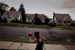 Hector Ortiz, age 9, tosses a football to his uncle John Veanus near their home at 430 Grandview in Bethlehem's Northside. Hector, who is one-half Puerto Rican, is one of many Hispanic children whose families have moved out of the poorer Southside and into the middle class white neighborhoods of the Northside, across the Lehigh River.